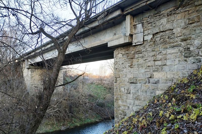 Vieux pont en pierre au-dessus d'une rivière peu profonde photo libre de droits