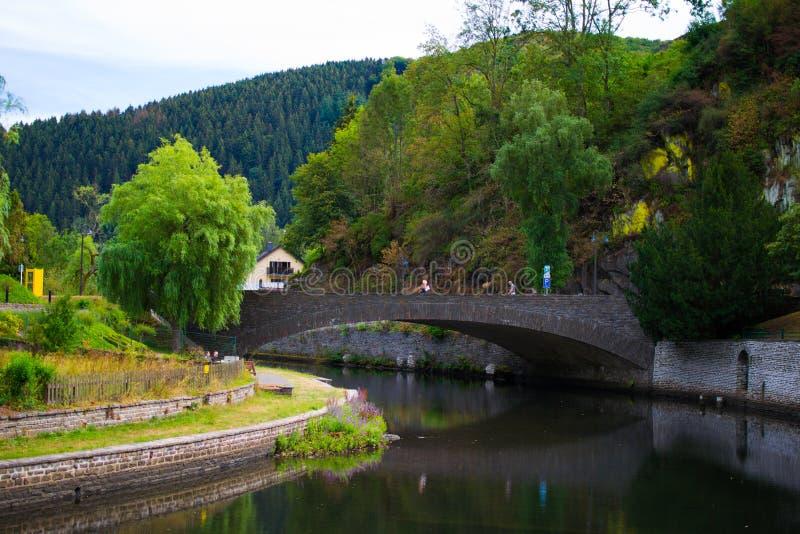 Vieux pont en pierre au-dessus de rivière sûre avec un passage couvert par la rive et la montagne et arbres au fond Esch Sur sûr, photos stock