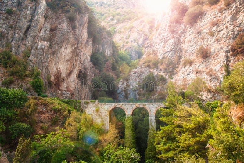 Vieux pont en pierre en montagnes au coucher du soleil photographie stock
