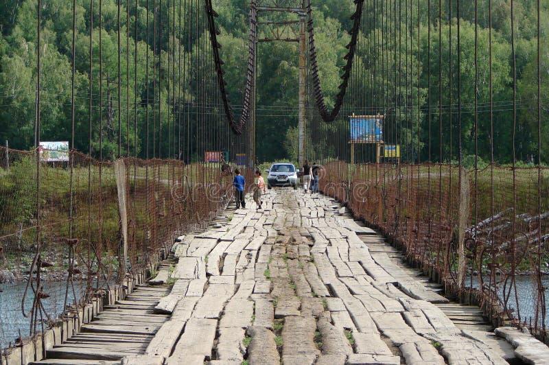 Vieux pont suspendu au-dessus de la rivière dans les montagnes d'Altai avec une voiture et un peuple image stock