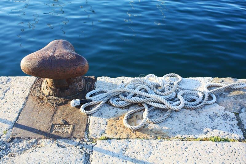 Vieux port rouillé sur la jetée de bateau avec la corde de mer dans le Pula photos libres de droits