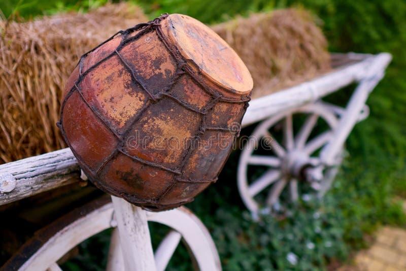 Vieux pot d'argile sur un chariot avec le foin photo stock