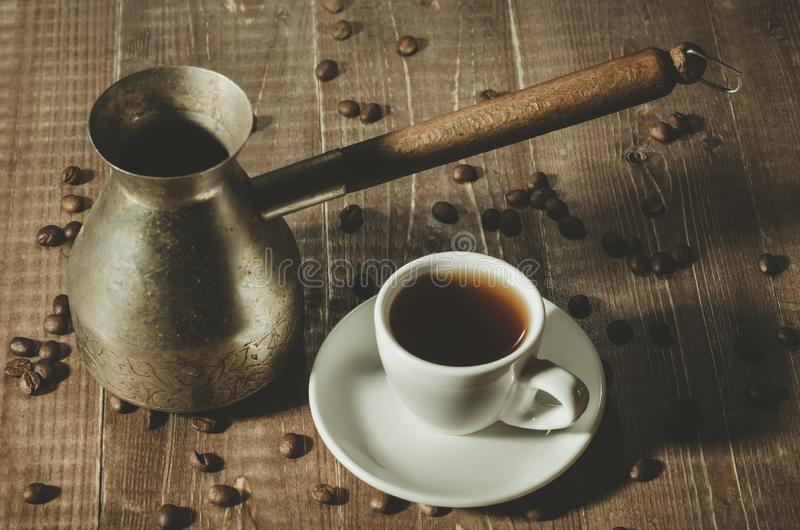 Vieux pot de café, tasse chaude et grains de café sur le backgrou rustique foncé photographie stock libre de droits