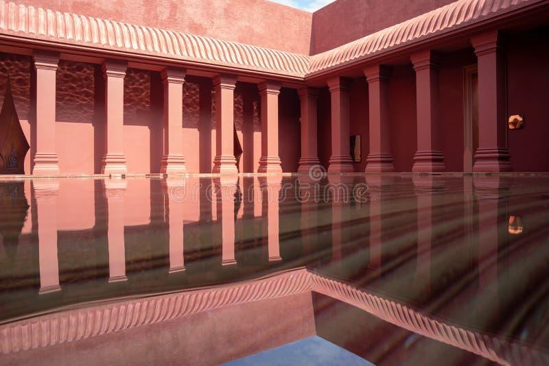 Vieux poteau rouge de cru appliqué entre le style oriental et occidental avec la piscine d'eau réflexe dans le secteur moyen photographie stock