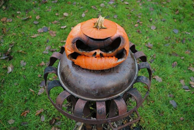 Vieux potiron brûlé de Halloween sur le panier de feu photos stock