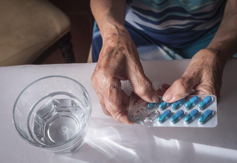 Vieux prenant la dose quotidienne de médicament à la maison image libre de droits