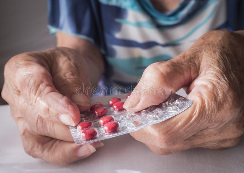 Vieux prenant la dose quotidienne de médicament à la maison images libres de droits