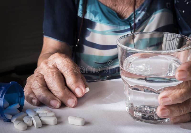 Vieux prenant la dose quotidienne de médicament à la maison photographie stock libre de droits
