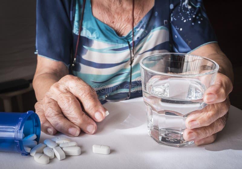 Vieux prenant la dose quotidienne de médicament à la maison image stock