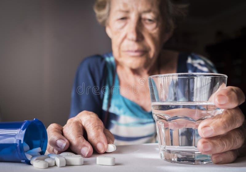 Vieux prenant la dose quotidienne de médicament à la maison photo stock
