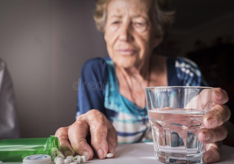 Vieux prenant la dose quotidienne de médicament à la maison photos stock