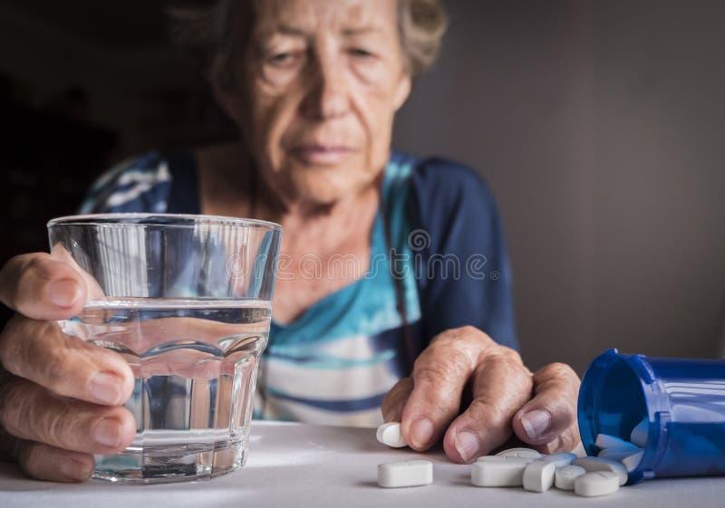 Vieux prenant la dose quotidienne de médicament à la maison photos libres de droits