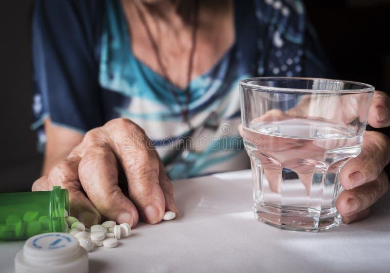Vieux prenant la dose quotidienne de médicament à la maison images stock