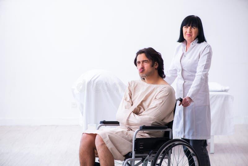 Vieux psychiatre féminin rendant visite au jeune patient masculin images libres de droits