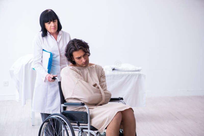 Vieux psychiatre féminin rendant visite au jeune patient masculin photographie stock