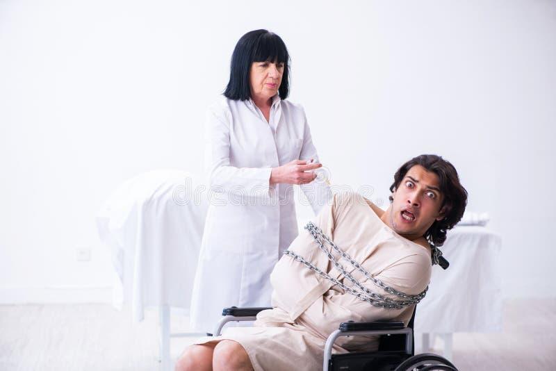 Vieux psychiatre féminin rendant visite au jeune patient masculin photographie stock libre de droits