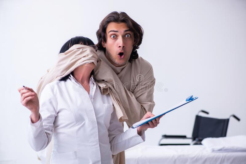 Vieux psychiatre féminin rendant visite au jeune patient masculin image stock