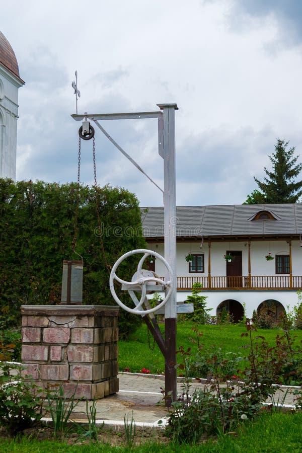 Vieux puits avec la roue et le seau de rotation manuelle en dehors du monastère de Cernica image stock