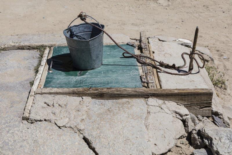 Vieux puits d'aspiration avec le seau dans Bulunkul dans le Tadjikistan photographie stock