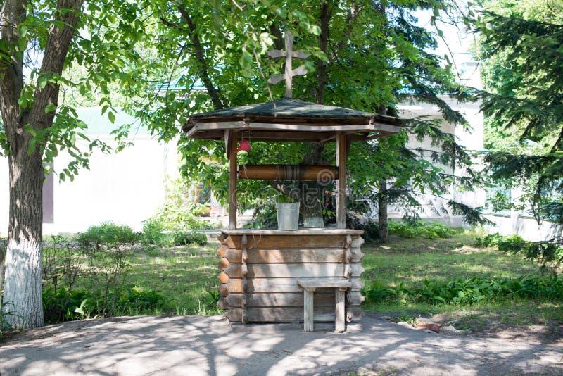 Vieux puits en bois avec une croix sur le toit et le seau parmi l'herbe verte dans le village photographie stock libre de droits