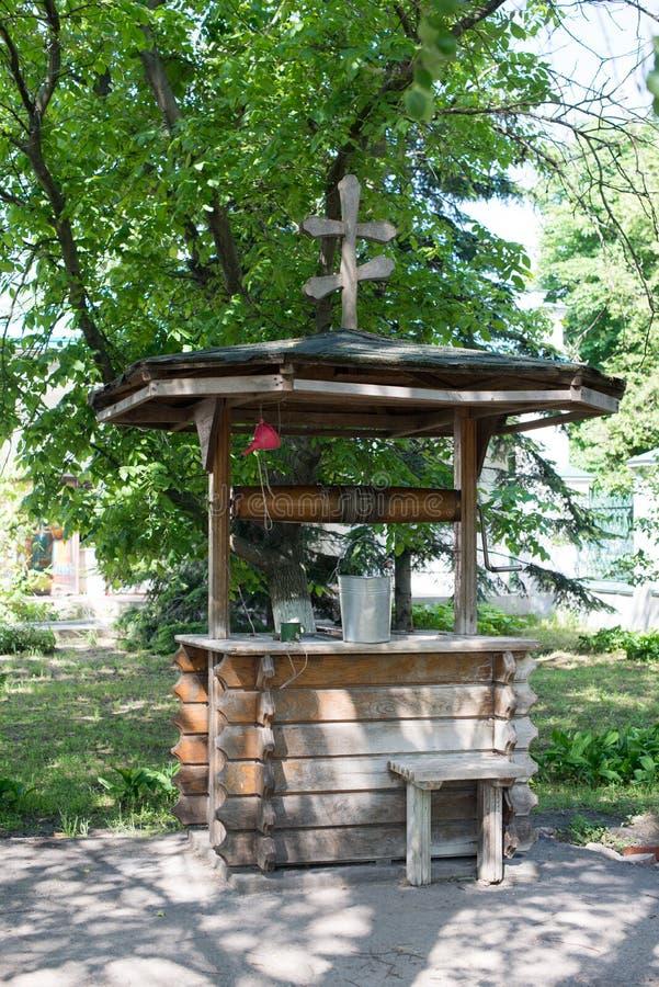 Vieux puits en bois avec une croix sur le toit et le seau parmi l'herbe verte dans le village image libre de droits