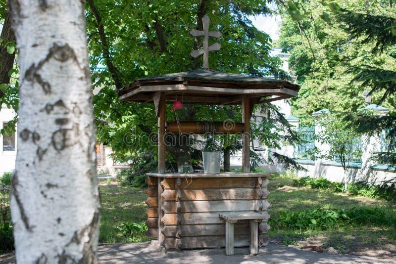 Vieux puits en bois avec une croix sur le toit et le seau parmi l'herbe verte dans le village photographie stock