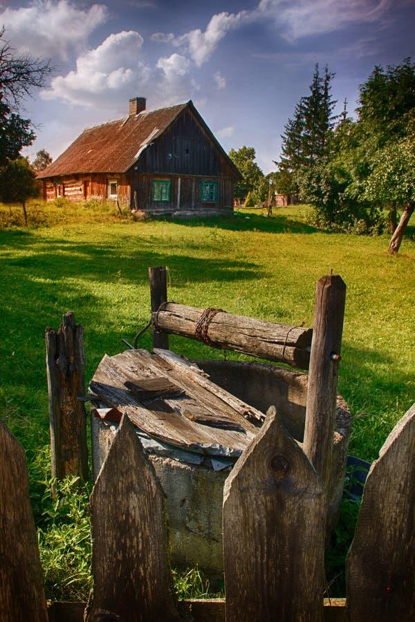 Vieux puits et maison photographie stock libre de droits