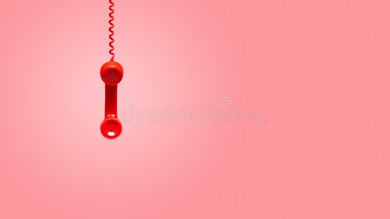 Vieux récepteur téléphonique rouge accrochant sur le fond rose photos stock