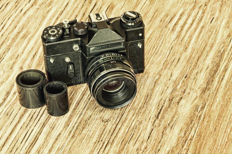 Vieux rétros appareil-photo de photo et bande de négatif sur film sur la table photo libre de droits