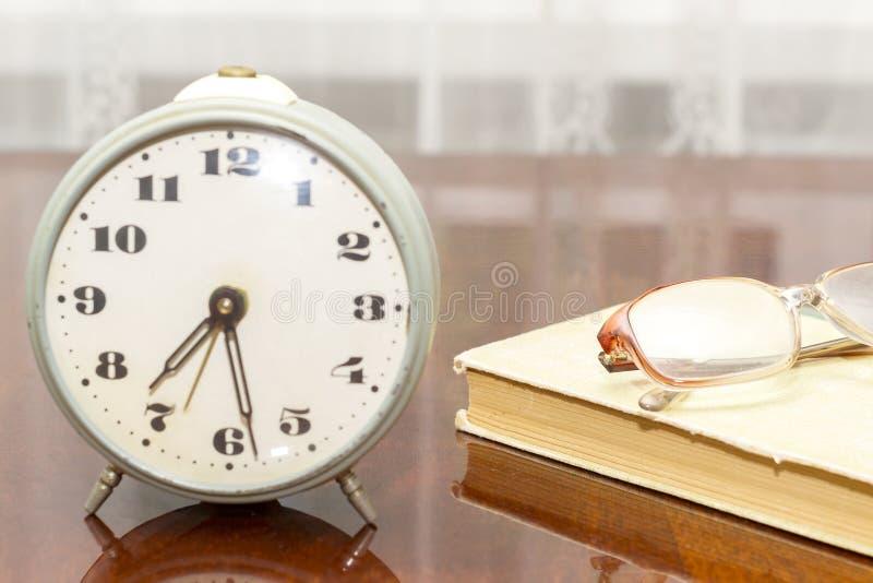 Vieux réveil en métal, verres, livre sur la vieille fin de table  image libre de droits