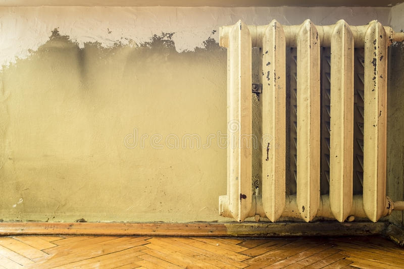 Vieux radiateur de fonte accrochant sur le mur photos stock