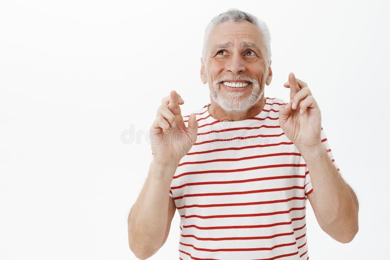 Vieux retraité masculin heureux et charismatique optimiste dans le T-shirt rayé soulevant des mains croisant des doigts pour la b images stock
