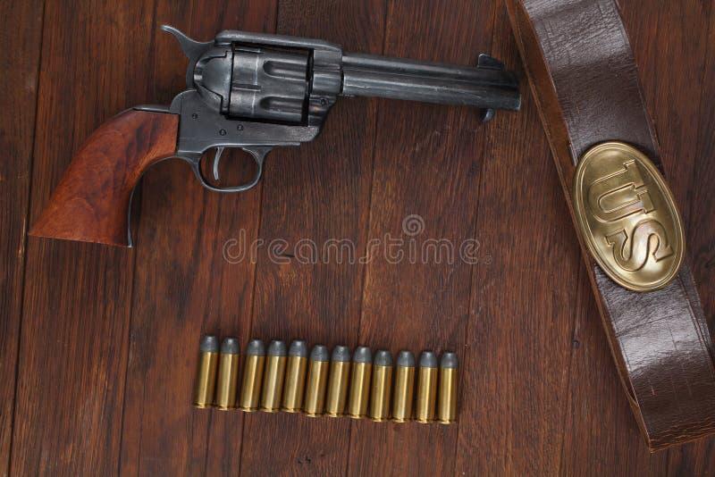 Vieux revolver avec des cartouches et U S Soldier& x27 d'armée ; ceinture de s avec une boucle photographie stock libre de droits