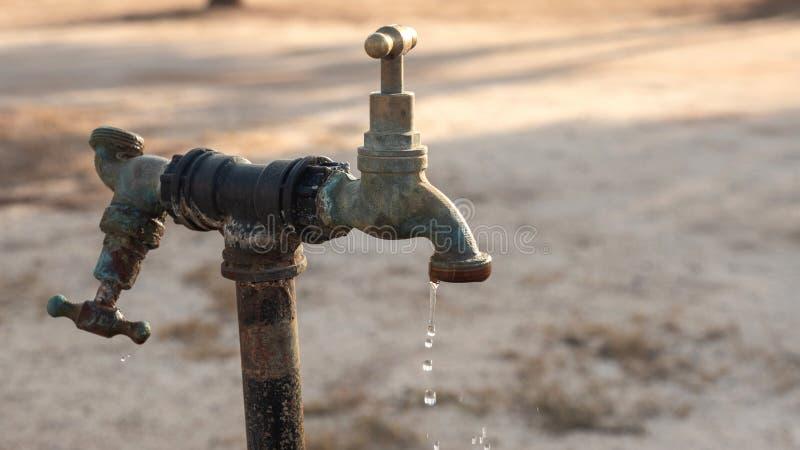 Vieux robinet dehors, s'égouttant des gouttelettes d'eau photos libres de droits