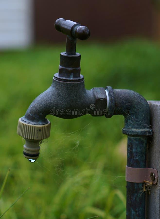 Vieux robinet sale s'égouttant une goutte de l'eau images stock