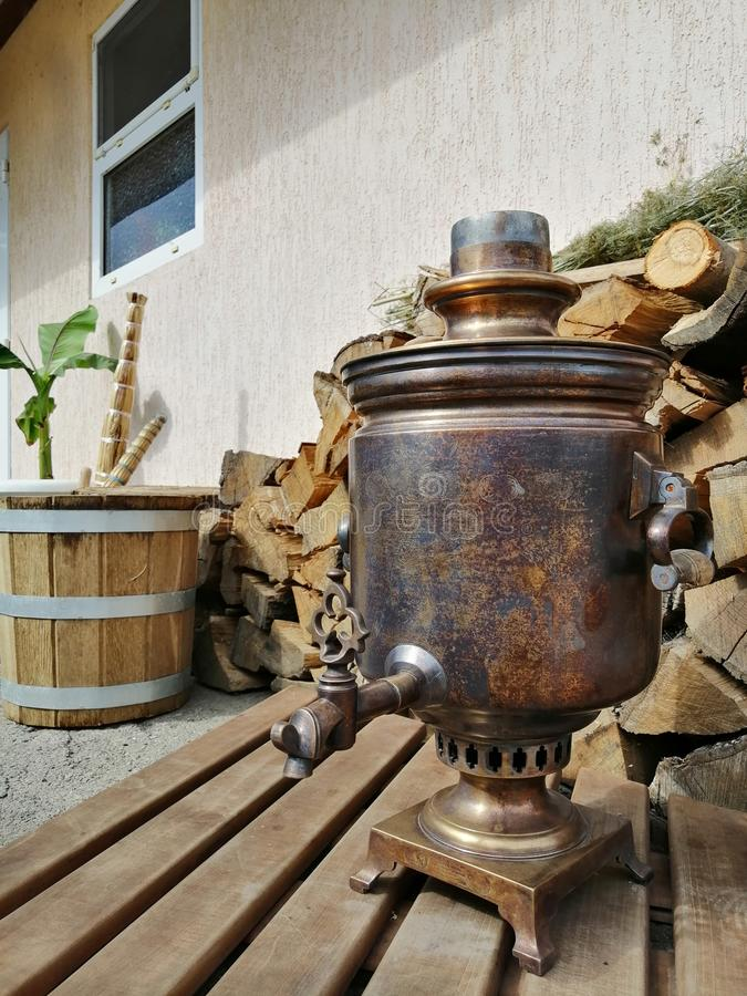Vieux samovar sur le fond du bois de chauffage photo stock