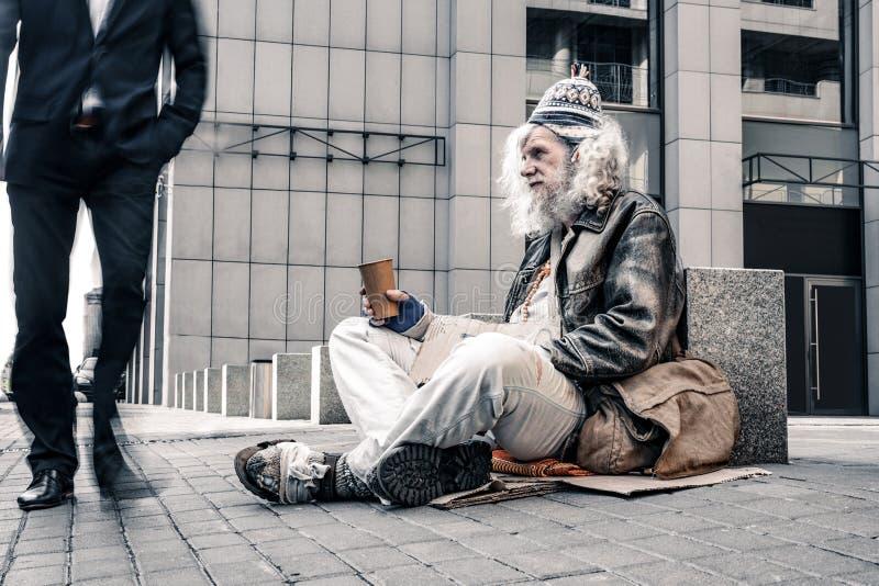 Vieux sans-abri aux cheveux gris malheureux s'asseyant sans mouvement sur la terre froide photo libre de droits