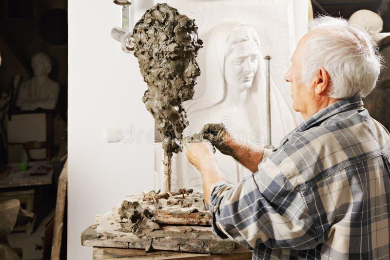 Vieux sculpteur effectuant la sculpture images libres de droits