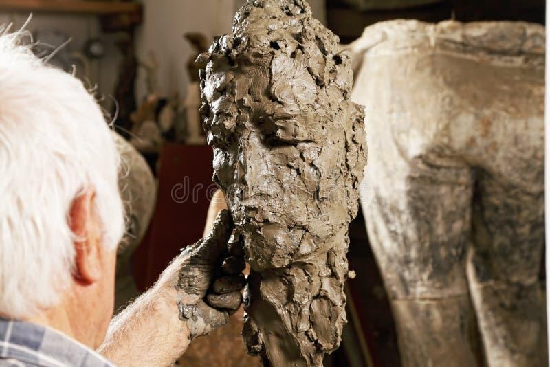 Vieux sculpteur modelant la sculpture image libre de droits