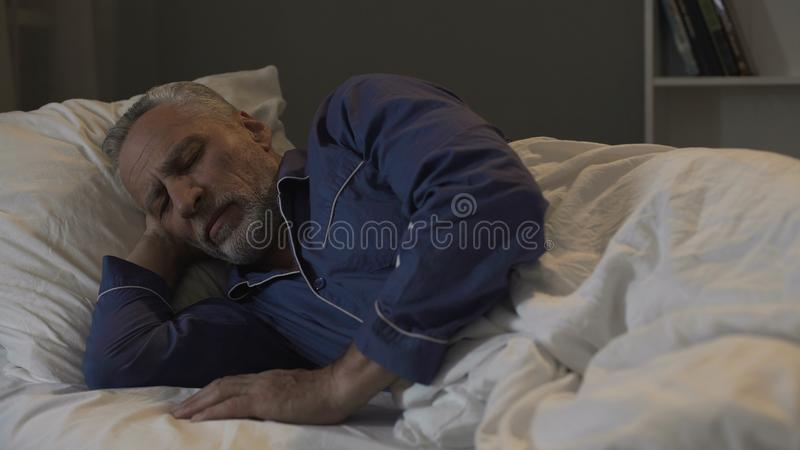 Vieux se situer masculin dans son lit et sommeil, temps de rétablissement et sommeil sain, nuit photos libres de droits
