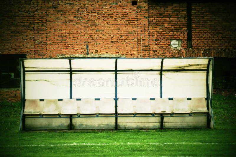 Vieux sièges en plastique sur le banc extérieur de joueurs de stade, chaises avec la peinture usée au-dessous du toit jaune photos libres de droits