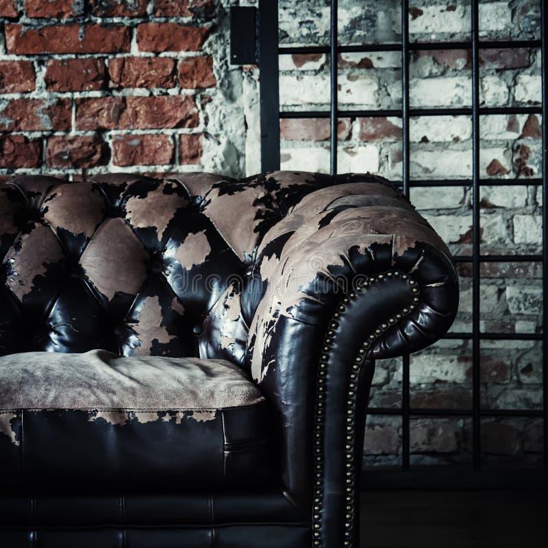 Vieux sofa de vintage sur le fond du mur de briques et des grilles, selectiv images libres de droits