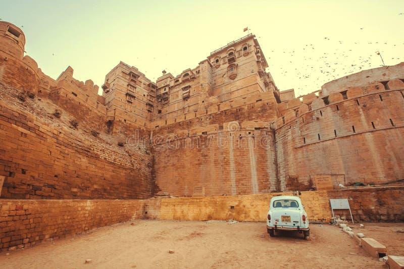Vieux stationnement blanc de voiture après le fort historique de Jaisalmer avec les tours en pierre dans le désert de Thar photo libre de droits