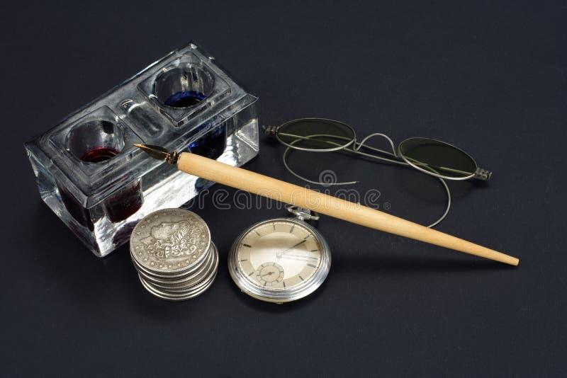 Vieux stylo-plume et encrier encastré avec les pièces en argent et montre de poche sur un fond noir photo stock