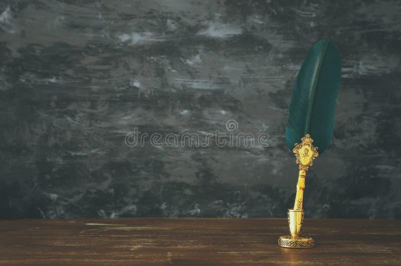 Vieux stylo vert d'encre de cannette de plume avec l'encrier encastré au-dessus du bureau en bois devant le fond noir de mur Styl images libres de droits