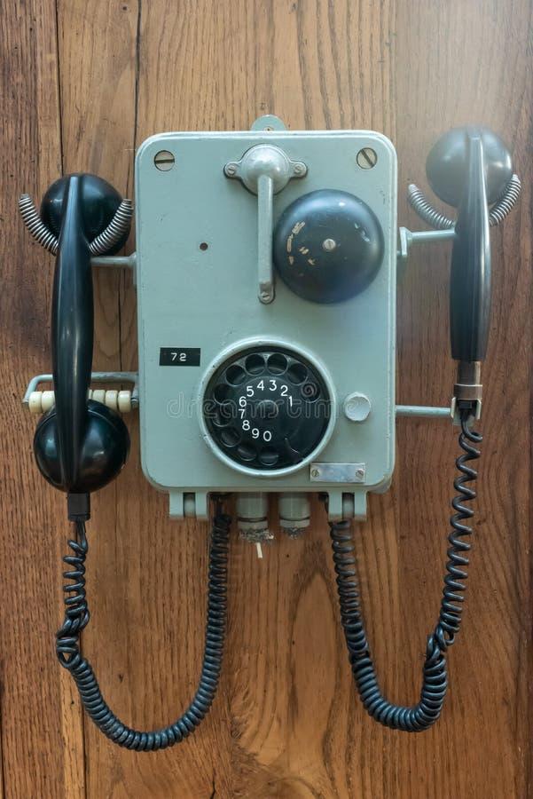 Vieux téléphone accrochant sur un mur en bois photos libres de droits