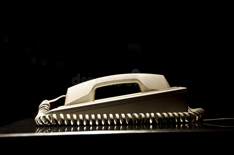 Vieux téléphone de vintage avec une corde en spirale, fond noir images stock