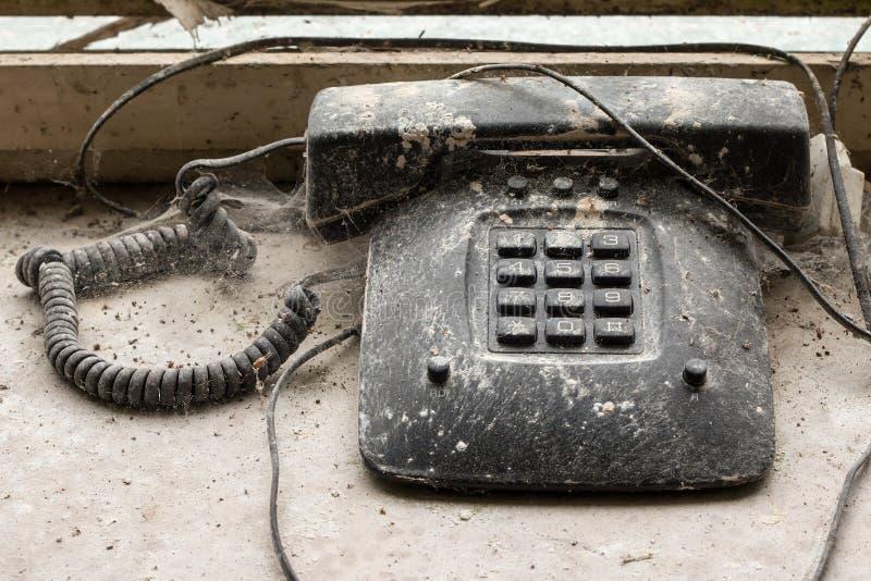 Vieux téléphone envahi avec des toiles d'araignée image libre de droits