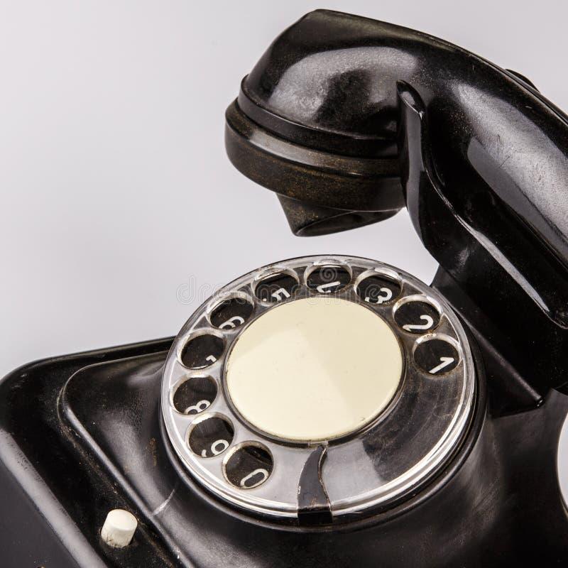 Vieux téléphone noir avec la poussière et éraflures sur le fond blanc photo libre de droits
