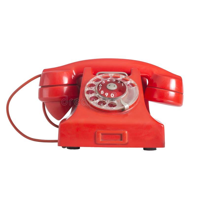 Vieux téléphone rouge avec le cadran rotatoire, d'isolement sur le fond blanc, Se photographie stock